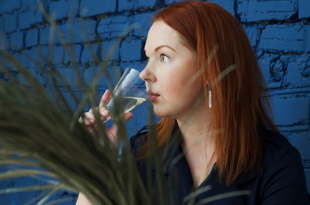 Jeune femme rousse boit pensivement du champagne de verre sur fond de mur de brique bleue.