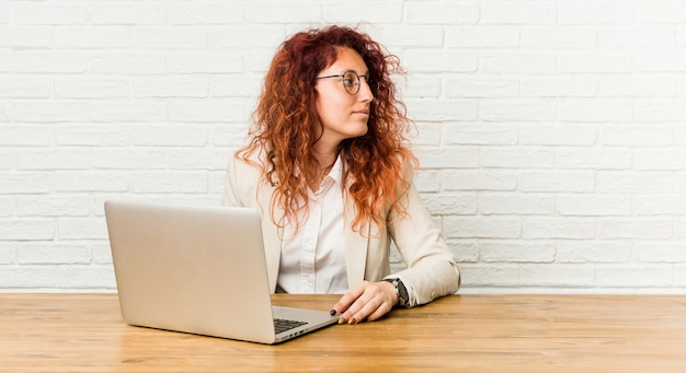 Jeune femme rousse bouclée travaillant avec son ordinateur portable semble de côté souriant, joyeux et agréable.