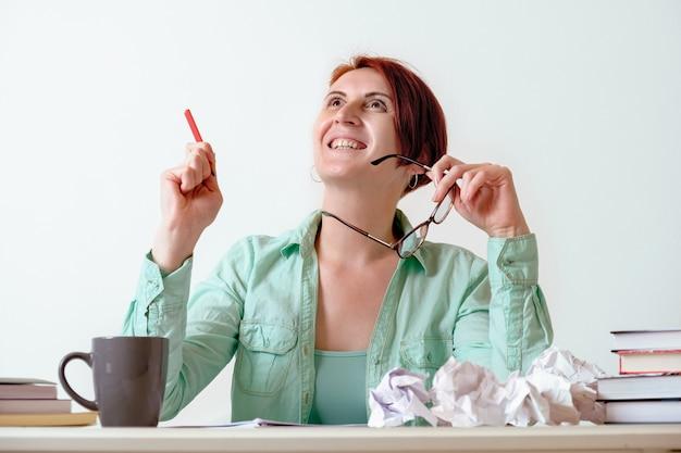Jeune femme rousse à un bureau avec un crayon dans les mains lève les yeux avec inspiration