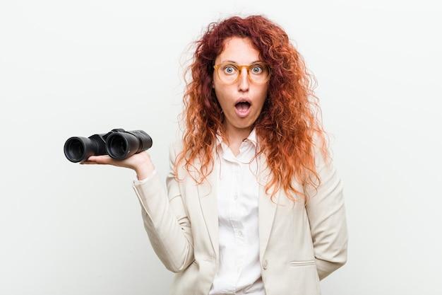 Jeune femme rousse business caucasien tenant une jumelle impressionné tenant copie espace sur la paume.
