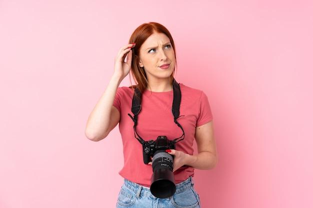 Jeune femme rousse avec une caméra professionnelle et réfléchissant