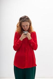 Jeune femme rousse caucasienne concentrée utilisant un téléphone portable, discutant sur le web