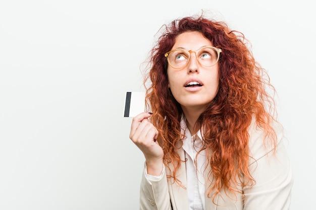 Jeune femme rousse caucasienne tenant une carte de crédit en essayant d'écouter les potins.