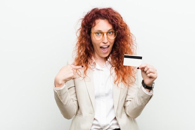 Jeune femme rousse caucasienne tenant une carte de crédit surpris en se montrant, souriant largement.
