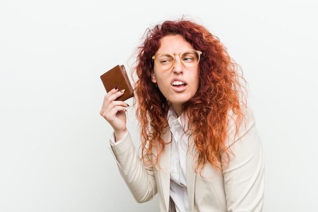 Jeune femme rousse caucasienne tenant un portefeuille en essayant d'écouter un commérage