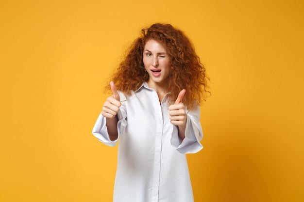 Jeune femme rousse en chemise blanche décontractée posant isolée sur un mur orange jaune