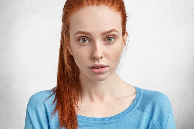 Jeune femme rousse avec chemise bleue