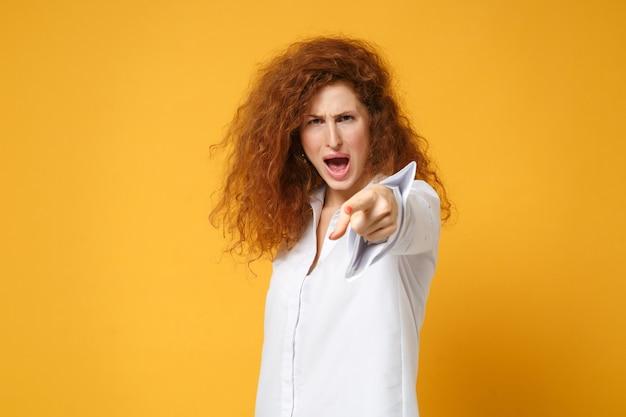 Jeune femme rousse en colère en chemise blanche décontractée posant isolée sur un mur orange jaune