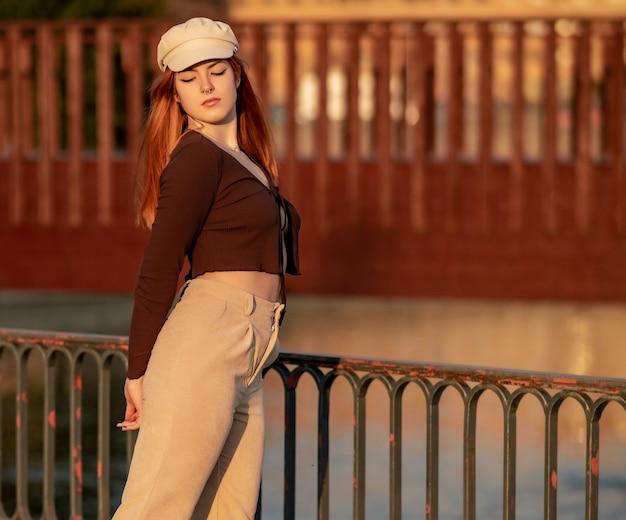 Jeune femme rousse dans un chapeau posant pendant le coucher du soleil dans le parc