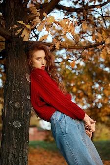 Jeune femme rousse dans un pull rouge se promène dans le parc. portrait de beauté automne d'une femme rousse à la mode au coucher du soleil