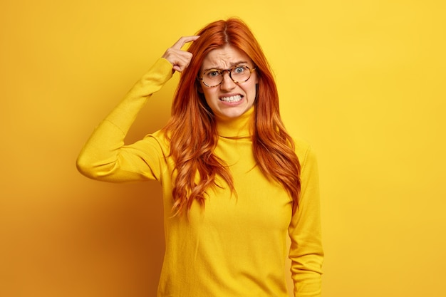 Une jeune femme rousse déçue a des doutes, se gratte la tête et serre les dents porte un col roulé décontracté a une mauvaise mémoire.