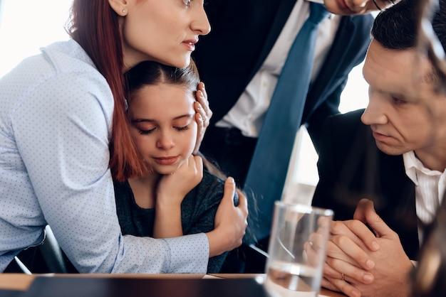 Jeune femme rousse étreignant une fille qui pleure.