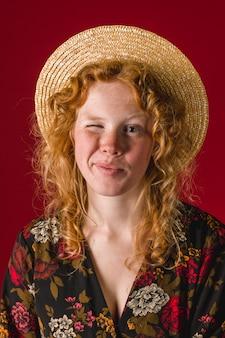 Jeune femme rousse faisant un clin d'oeil et regardant la caméra