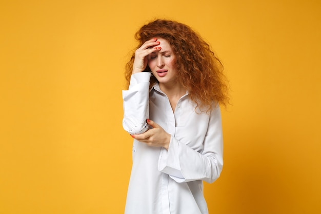 Jeune femme rousse fatiguée et mécontente en chemise blanche décontractée posant isolée sur un mur orange jaune