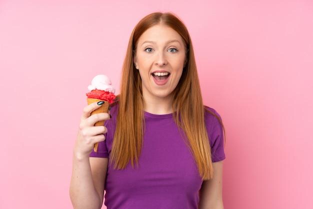 Jeune femme rousse avec une glace au cornet avec surprise et expression faciale choquée