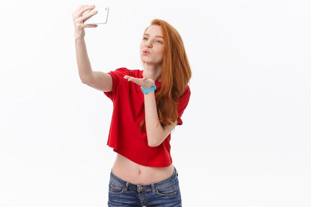 Jeune femme rousse heureuse isolée sur fond de mur blanc faire selfie