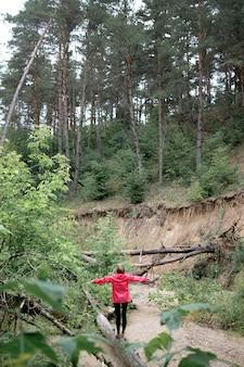 Jeune femme rousse en imperméable rose marchant le journal en forêt