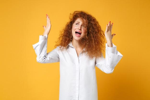 Jeune femme rousse inquiète mécontente en chemise blanche posant isolée sur un mur orange jaune