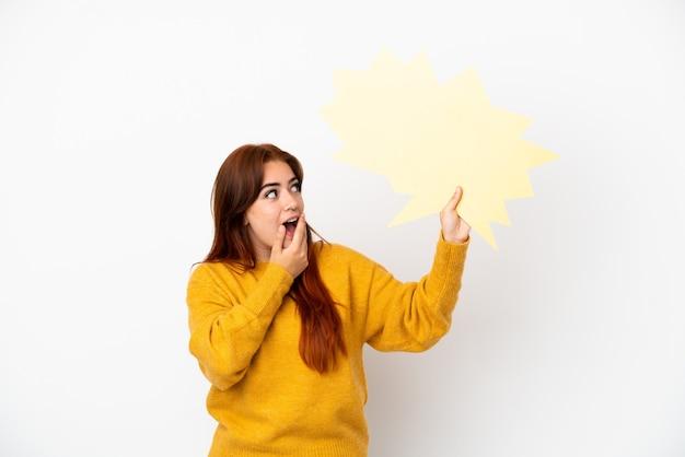 Jeune femme rousse isolée sur fond blanc tenant une bulle de dialogue vide avec une expression surprise