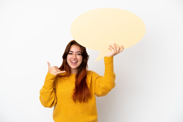 Jeune femme rousse isolée sur fond blanc tenant une bulle de dialogue vide et faisant un geste de téléphone