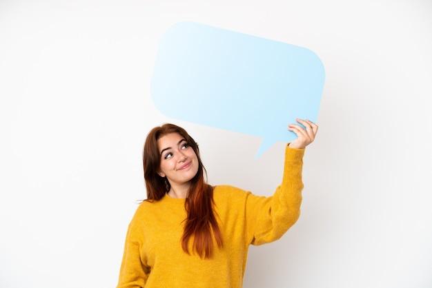 Jeune femme rousse isolée sur fond blanc tenant une bulle de dialogue vide
