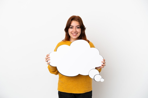 Jeune femme rousse isolée sur fond blanc tenant une bulle de pensée