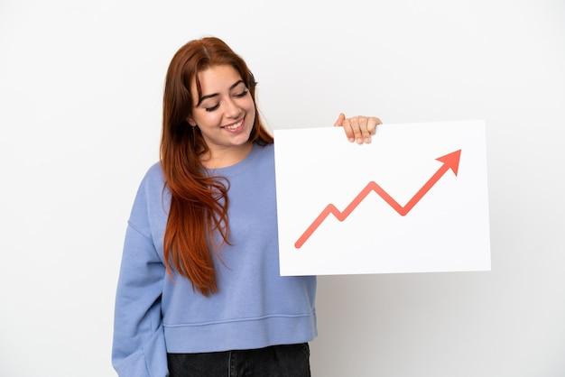 Jeune femme rousse isolée sur fond blanc tenant une pancarte avec un symbole de flèche de statistiques croissante avec une expression heureuse