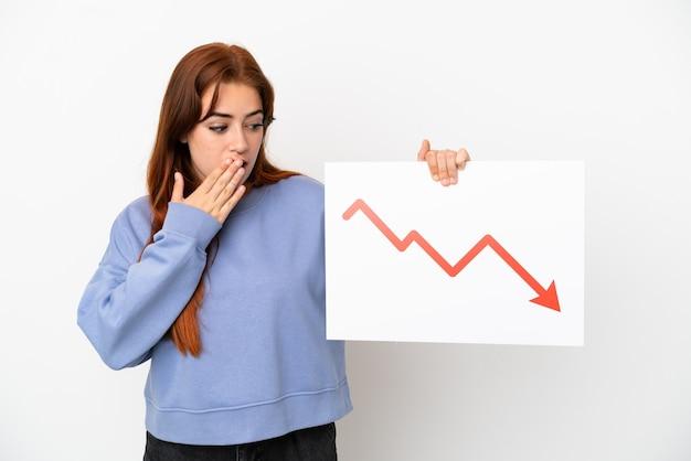 Jeune femme rousse isolée sur fond blanc tenant une pancarte avec un symbole de flèche de statistiques décroissantes avec une expression surprise