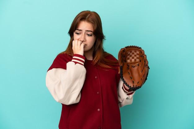 Jeune femme rousse jouant au baseball isolé sur fond bleu ayant des doutes