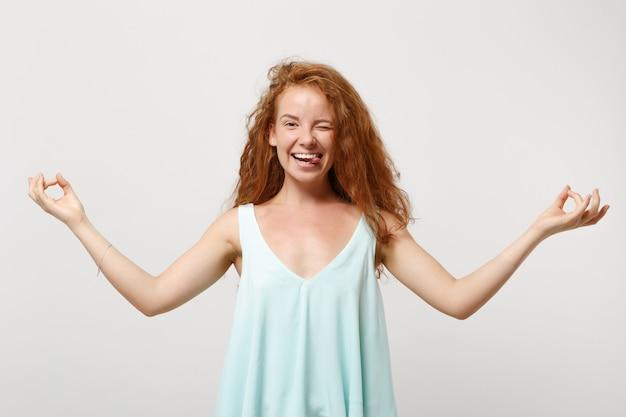 Jeune femme rousse joyeuse dans des vêtements légers décontractés posant isolé sur fond blanc. concept de mode de vie des gens. maquette de l'espace de copie. tenez-vous la main dans un geste de yoga, relaxant en méditant, montrant le pouce.