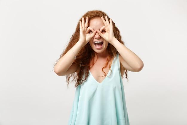 Jeune femme rousse joyeuse dans des vêtements légers décontractés posant isolé sur fond de mur blanc. concept de mode de vie des gens. maquette de l'espace de copie. se tenir la main près des yeux, imiter des lunettes ou des jumelles.