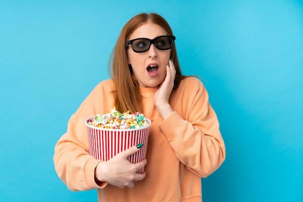 Jeune femme rousse avec des lunettes 3d et tenant un gros seau de pop-corn
