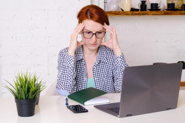 Jeune femme rousse avec des lunettes est assise devant un ordinateur portable avec ses doigts sur ses tempes