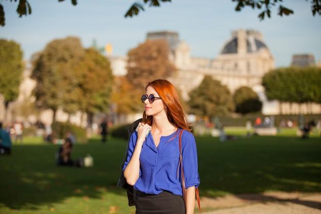 Jeune femme rousse à lunettes de soleil marchant dans les rues parisiennes
