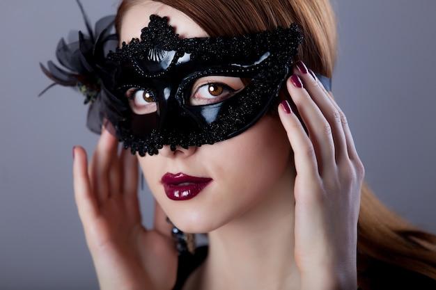 Jeune femme rousse en masque de carnaval sur fond gris