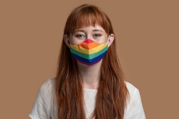 Jeune femme rousse avec masque médical arc-en-ciel