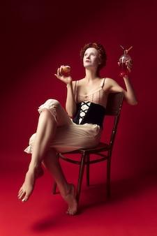 Jeune femme rousse médiévale comme une duchesse en corset noir et vêtements de nuit assis sur une chaise sur l'espace rouge avec un verre et un beignet