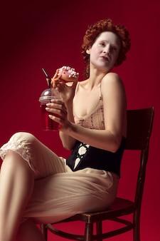 Jeune femme rousse médiévale en tant que duchesse en corset noir et vêtements de nuit assis sur une chaise sur un mur rouge avec un verre et un beignet. concept de comparaison des époques, de la modernité et de la renaissance.