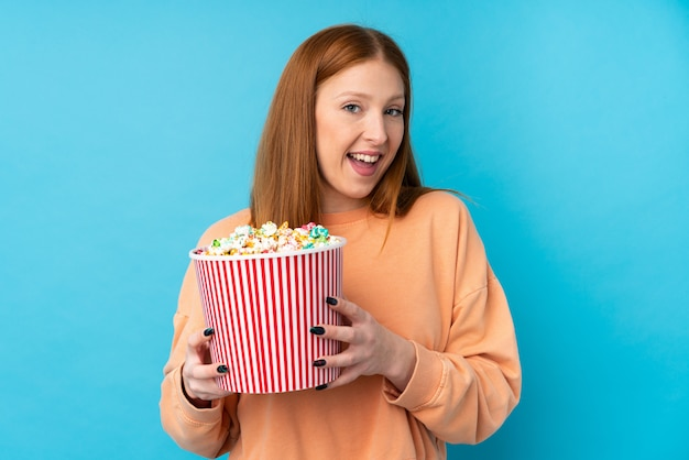 Jeune femme rousse sur mur isolé tenant un gros seau de pop-corn