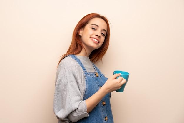Jeune femme rousse sur mur isolé, tenant une tasse de café