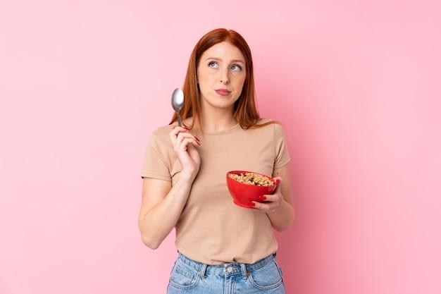 Jeune femme rousse sur mur rose isolé, tenant un bol de céréales et de la pensée