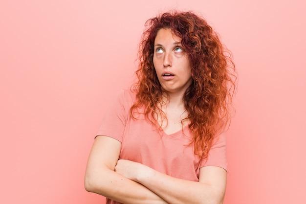 Jeune femme rousse naturelle et authentique fatiguée d'une tâche répétitive.