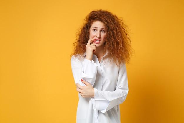 Jeune femme rousse nerveuse en chemise blanche décontractée posant isolée sur un mur orange jaune