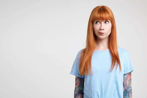 Jeune femme rousse perplexe avec des tatouages tordant sa bouche tout en regardant pensivement de côté, gardant ses mains le long du corps tout en posant sur fond blanc