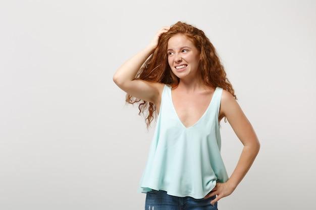 Jeune femme rousse préoccupée dans des vêtements légers décontractés posant isolé sur fond de mur blanc portrait en studio. concept de mode de vie des gens. maquette de l'espace de copie. à côté de mettre la main sur la tête.