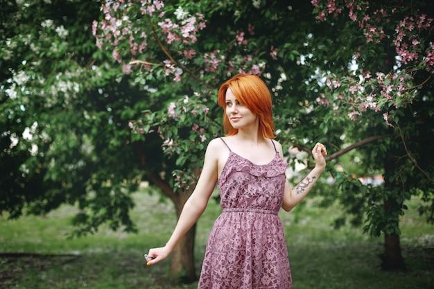 Jeune femme rousse près de l'arbre de printemps en fleurs, beauté naturelle
