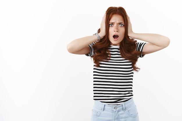 Une jeune femme rousse prise en embuscade et choquée en t-shirt rayé, tient les mains sur la tête, fronce les sourcils nerveusement, bouche ouverte prise en embuscade et inquiète, debout déçue et affligée