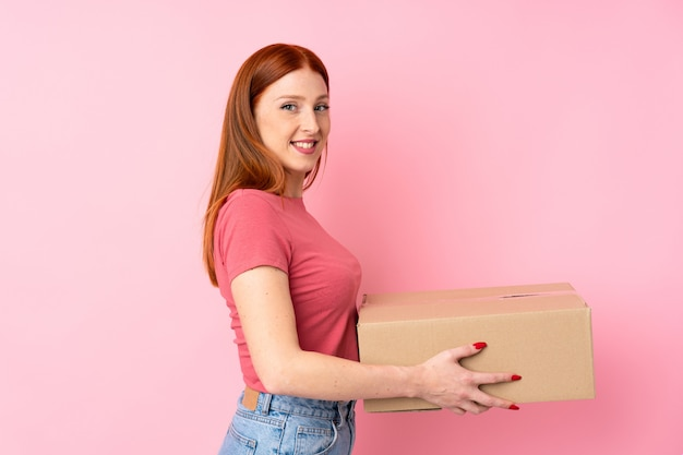 Jeune femme rousse sur rose isolé tenant une boîte pour la déplacer vers un autre site