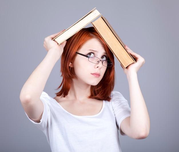 Jeune femme rousse se cachant sous un livre sur fond gris