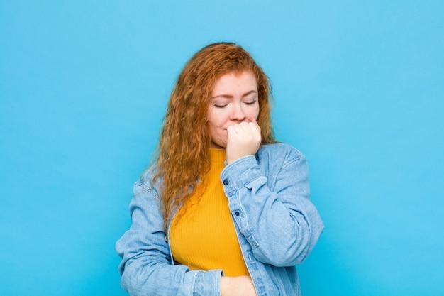 Jeune femme rousse se sentir sérieuse, réfléchie et inquiète, regardant de côté avec la main pressée contre le menton contre le mur bleu